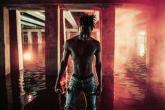 Los soportes africanos jovenes del hombre bajo el puente y controles colorearon la bomba de humo roja fotografía de archivo libre de regalías
