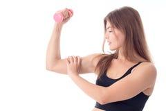 Los soportes atléticos jovenes de una muchacha de lado y mantenido la bola para el bíceps se aíslan en el fondo blanco Imagen de archivo