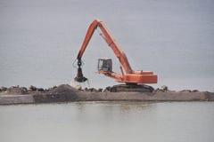 Los soportes de la grúa en la costa artificial vierten la arena en la orilla del río artificial Imagenes de archivo