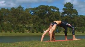 Los soportes de la mujer en actitud de la yoga en hierba apuntalan cerca del lago
