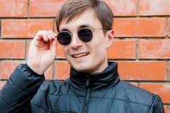Los soportes de un hombre joven que se inclinan contra una pared de ladrillo ajustan sus gafas de sol fotos de archivo libres de regalías