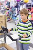 Los soportes del muchacho en la rueda de ardilla del instructor en deportes hacen compras Fotografía de archivo