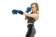 Los soportes delgados de la muchacha de lado en guantes de boxeo se aíslan en un fondo blanco Foto de archivo