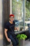 Los soportes hermosos del árabe del hombre joven cerca de sonrisas de la pared, disfrutan y ho Imagen de archivo libre de regalías
