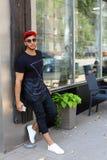 Los soportes hermosos del árabe del hombre joven cerca de sonrisas de la pared, disfrutan y ho Fotografía de archivo libre de regalías