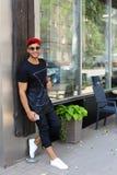 Los soportes hermosos del árabe del hombre joven cerca de sonrisas de la pared, disfrutan y ho Imagen de archivo