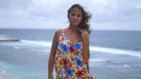 Los soportes morenos jovenes pensativos de la mujer en una roca por el océano en tiempo de la tormenta miran la cámara Cámara len metrajes