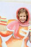 Los stucks sonrientes de la muchacha dirigen en paisaje de la madera contrachapada en la feria Foto de archivo