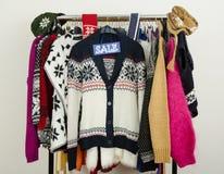 Los suéteres lindos del invierno exhibidos en suspensiones con una venta grande firman Fotos de archivo
