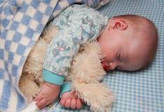 Los sueños del niño que abrazan un juguete Imagen de archivo
