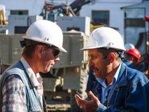 Los técnicos de la ingeniería son discusión Los empleados del ` s de la compañía en los cascos blancos Imagen de archivo