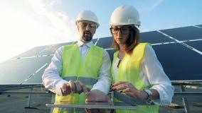 Los técnicos están discutiendo el modelo del proyecto de construcción cerca de una construcción solar Concepto verde de la energí almacen de video