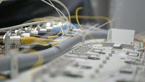 Los técnicos están instalando la fibra óptica con las bridas de plástico almacen de video