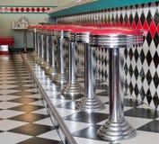 Los taburetes contrarios en una fila en los años 50 labran el comensal Imagen de archivo libre de regalías