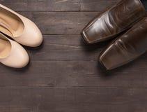 Los tacones altos y los zapatos de cuero están en fondo de madera Foto de archivo libre de regalías