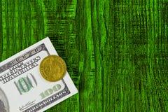 Los tacos de cientos billetes de dólar y un dólar del oro del top en un fondo verde Foto de archivo libre de regalías