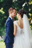 Los tactos bonitos de la novia preparan el cuello del ` s stnading debajo de un árbol verde foto de archivo