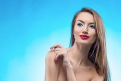 Los tactos sonrientes de la muchacha de los labios rojos rubios hermosos por los fingeres fa Imágenes de archivo libres de regalías