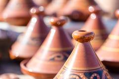 Los tajins marrones hechos a mano de la arcilla para el cocido al vapor al vapor de la comida arreglaron en filas con referencia  Foto de archivo libre de regalías