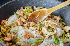 Los tallarines asiáticos con las flechas del ajo y de los pedazos de carne se fríen en una sartén foto de archivo