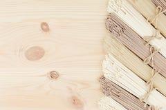 Los tallarines asiáticos crudos en el tablero de madera beige suave con la copia espacian como marco decorativo de la frontera, v Imágenes de archivo libres de regalías