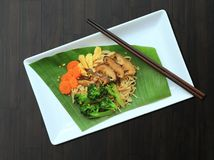 Los tallarines de arroz sofritos en el top blanco de la hoja del plátano la planta son un nogal negro de madera foto de archivo libre de regalías