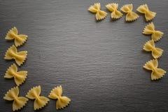 Los tallarines de Farfalle en la pizarra ennegrecen al tablero con el espacio de la copia imagen de archivo