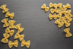 Los tallarines de Farfalle en la pizarra ennegrecen al tablero con el espacio de la copia foto de archivo