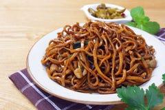 Los tallarines del mein de Yi sofrieron con la salsa oscura del caramelo Fotos de archivo