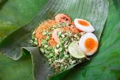 Los tallarines fritos de la leche de coco con servicio del camarón en un plátano salen de estilo tailandés tradicional fotografía de archivo
