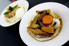 Los tallarines o la verdura tailandeses de la harina de arroz pusieron al lado de la sopa picante de los órganos de los pescados Imágenes de archivo libres de regalías