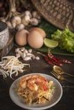 Los tallarines o los tailandeses fritos tailandeses del cojín con el camarón en la placa blanca colocada en la tabla de madera al imagen de archivo