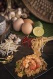 Los tallarines o los tailandeses fritos tailandeses del cojín con el camarón en la placa negra colocada en la tabla de madera all imagen de archivo libre de regalías