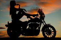 Los talones de la motocicleta de la mujer de la silueta suben la barbilla de la mano Imagen de archivo libre de regalías