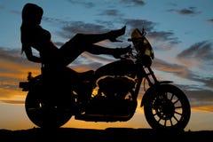 Los talones de la motocicleta de la mujer de la silueta suben la mano abajo Fotos de archivo libres de regalías