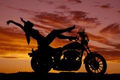 Los talones de la motocicleta de la mujer de la silueta suben las manos detrás Fotos de archivo