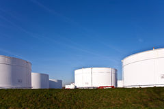 Los tanques blancos en granja del tanque con el cielo azul Imagenes de archivo