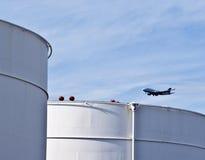Los tanques blancos en granja del tanque con el cielo azul y los aviones inminentes Imagen de archivo