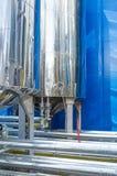 Los tanques del metal con las grúas en la fábrica Imagen de archivo libre de regalías