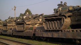 Los tanques rusos del engranaje militar se cargan encendido a los railcars y se preparan para el transporte del campo a través metrajes
