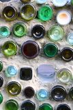 Los tarros de cristal coloreados adornan un muro de cemento blanco imágenes de archivo libres de regalías