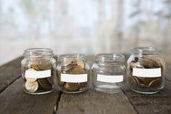 Los tarros de cristal con el dinero acuñan la rublo y la etiqueta engomada vacía Foto de archivo libre de regalías