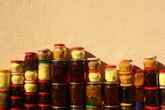 Los tarros de cristal con la miel y los conos hechos en casa tradicionales del pino atascan Imagenes de archivo