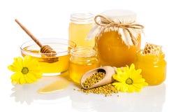 Los tarros de la miel con los panales, bol de vidrio con la miel Imagen de archivo