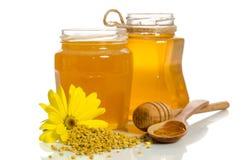 Los tarros de miel cerca de una pila de polen y de flor Imagen de archivo libre de regalías