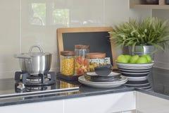 Los tarros del pote y de las pastas del acero inoxidable en negro rematan al revés Imagen de archivo