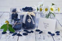 Los tarros y las botellas con la baya de la madreselva y la nota del vintage con el texto le aman Foto de archivo