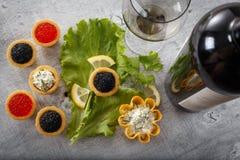 Los Tartlets llenaron de la ensalada roja y negra del caviar y de la alga marina con una copa de vino y una botella contra fondo  Fotografía de archivo libre de regalías