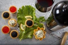 Los Tartlets llenaron de la ensalada roja y negra del caviar y de la alga marina con una copa de vino y una botella contra fondo  Imagen de archivo