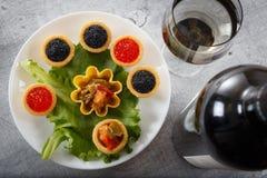 Los Tartlets llenaron de la ensalada roja y negra del caviar y de la alga marina en la placa blanca contra fondo de madera rústic Fotos de archivo